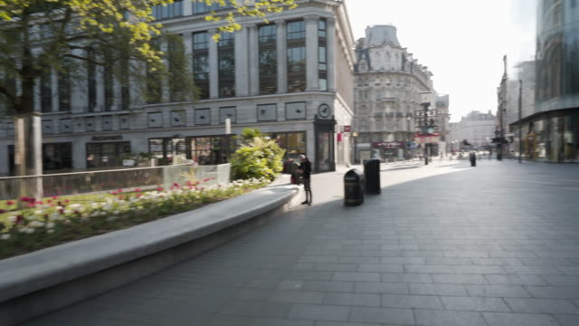 the camera pans through a deserted leicester square in central london in spring - leicester stock videos & royalty-free footage