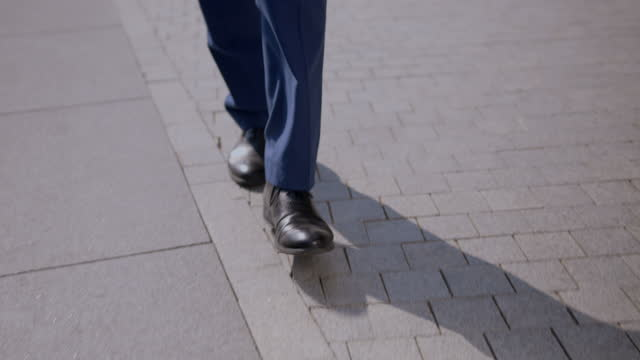 the camera shooting a close-up of the legs of a businessman, a manager, walking in a classic blue suit and brown shoes on a clean paving stone in the city center, on a sunny day. - full suit stock videos & royalty-free footage