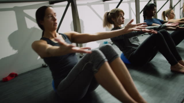 the camera slides past a multi-ethnic group of women in their twenties leaning back on fitness balls with their hands outstretched at an exercise studio - pilates stock videos and b-roll footage