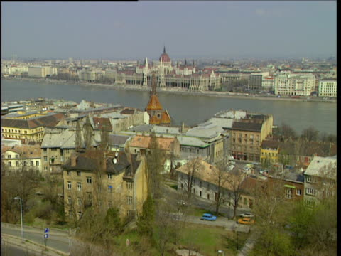 the camera slowly zooms in and out of the parliament building in budapest and also takes a sweeping shot from the building to the chain bridge - chain bridge suspension bridge stock videos & royalty-free footage