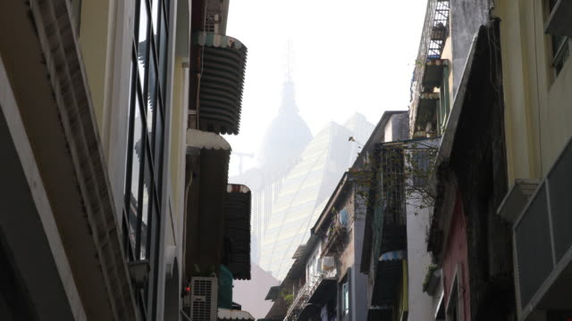 the camera swings down showing casinos high-rises in the foggy background and people walking up and down a narrow street with chinese signs and... - high street stock-videos und b-roll-filmmaterial