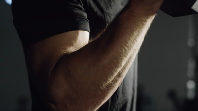 the camera tilts down as an attractive caucasian man in his twenties with a beard performs bicep curls with a dumbbell in a dramatically lit gym (tight shot) - bicep stock videos & royalty-free footage