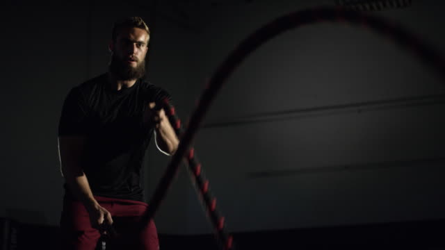 the camera tilts up to reveal an attractive caucasian man in his twenties with a beard doing battle rope exercises in a dramatically lit gym (medium shot) - battle stock videos & royalty-free footage