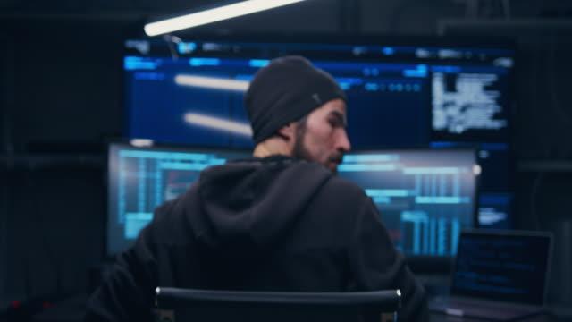 die kamera zoomt von hinten auf den hacker. der hacker dreht sich um und fühlt jemanden hinter sich. er befürchtet, dass sein versteck entdeckt wird und das fbi ihn finden wird. - e mail stock-videos und b-roll-filmmaterial