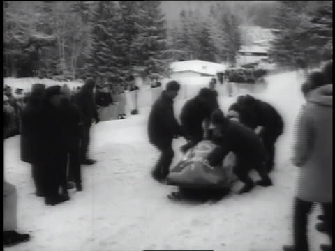 the canadians finish first in a bobsled race; a montage shows american and austrian medal winners in skiing. - bobsleighing stock videos & royalty-free footage