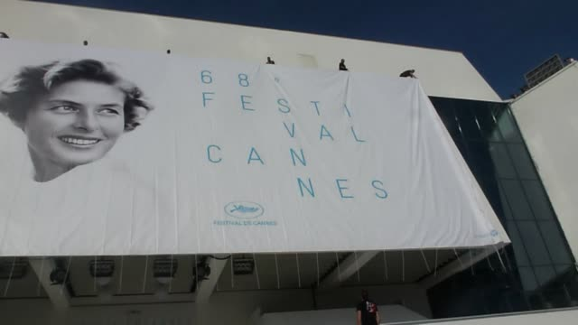 the cannes film festival's 2015 official poster is unveiled on the front of the palais des festivals showing the swedish born actress ingrid bergman - festival poster stock videos & royalty-free footage