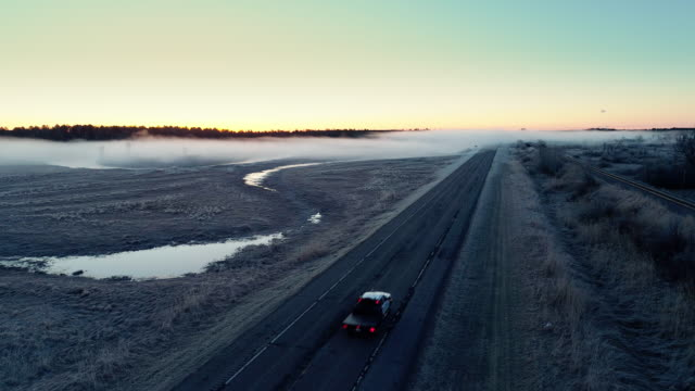 the car driving on the road covered by fog in chippewa national forest, minnesota, in the early cold morning in spring, with fog and haze. aerial drone video with the forward camera motion, following the car on the road. - minnesota stock videos & royalty-free footage