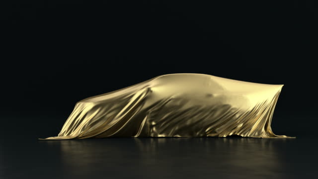 the car is covered with a gold cloth on a black background. the fabric falls from the vehicle but under it is nothing. - wrapped stock videos & royalty-free footage