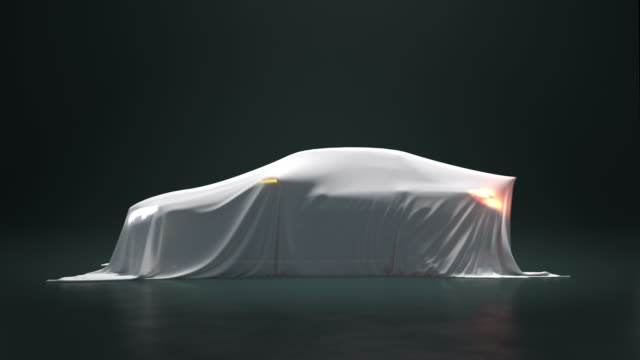 the car is covered with a white cloth on a black background. the fabric falls from the vehicle but under it is nothing. - motor stock videos & royalty-free footage