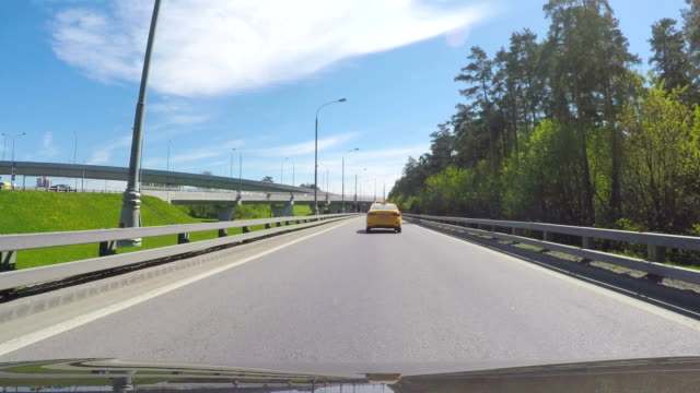 The car moves on a sunny summer day on the road junction behind the taxi