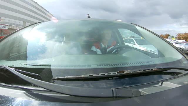 車はショッピングセンターの近くの駐車場に乗る。 - フロントガラス点の映像素材/bロール