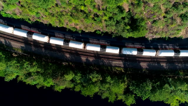The cargo train on the railroad in Appalachian mountain along the Lehigh River, near by Jim Thorpe, Pennsylvania, USA. Aerial footage.