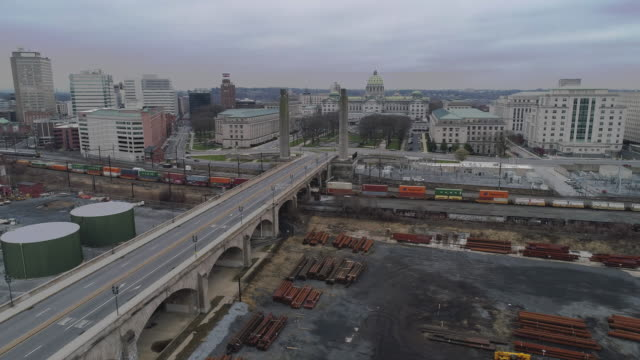 the cargo train passing in front of the pennsylvania state capitol complex trough the industrial zone which is now deserted because of covid-19 novel coronavirus outbreak.  drone video with the panoramic camera motion. - industrial district stock videos & royalty-free footage