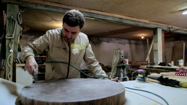 vídeos y material grabado en eventos de stock de el carpintero limpia la superficie de madera de la mesa del polvo. - ropa protectora