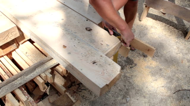 the carpenter makes measurements on a wooden beam. - roof beam stock videos & royalty-free footage