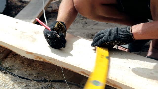 vídeos de stock, filmes e b-roll de o carpinteiro faz medições em uma placa de madeira. - braço humano