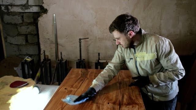 the carpenter polishes the wooden surface of the table. - finishing stock videos & royalty-free footage