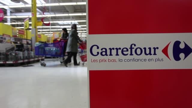 vidéos et rushes de the carrefour logo sits on the side of a display case inside a carrefour sa supermarket in portet sur garonne, near toulouse, as shoppers walk past,... - carrefour