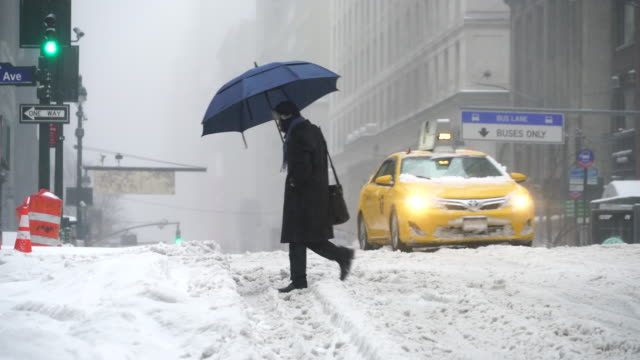 the cars run and pedestrians walk on the road, which is in deep snow at 34th street during the snowstorm in the morning on mar. 14 2017. - 状態点の映像素材/bロール