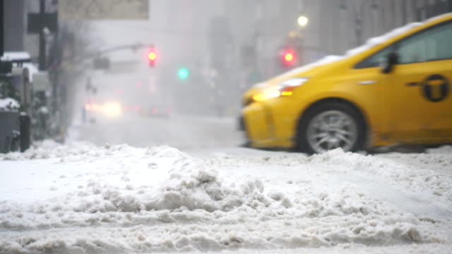the cars run and pedestrians walk on the road, which is in deep snow at 34th street during the snowstorm in the morning on mar. 14 2017. - 34th street stock videos and b-roll footage