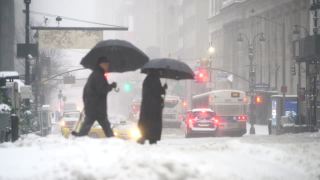 the cars run and pedestrians walk on the road, which is in deep snow at 34th street during the snowstorm in the morning on mar. 14 2017. - sturm frau stock-videos und b-roll-filmmaterial