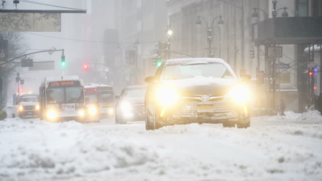 the cars run on the road, which is in deep snow at union square and 14th street during the snowstorm in the morning on mar. 14 2017. - union square new york city stock videos and b-roll footage