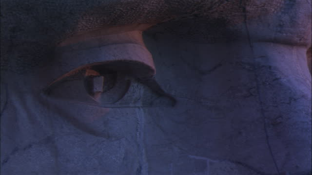 the carved eyes of george washington stare out from mount rushmore in south dakota. - ジョージ・ワシントン点の映像素材/bロール