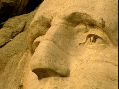 the carved face of president george washington gazes out from mount rushmore. - mt rushmore national monument stock videos & royalty-free footage