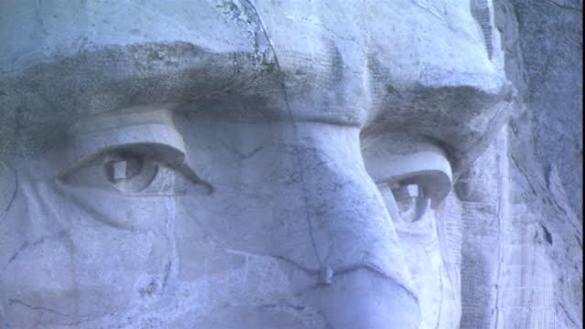 the carved face of u.s. president abraham lincoln at mount rushmore gazes across south dakota. - south dakota stock videos & royalty-free footage