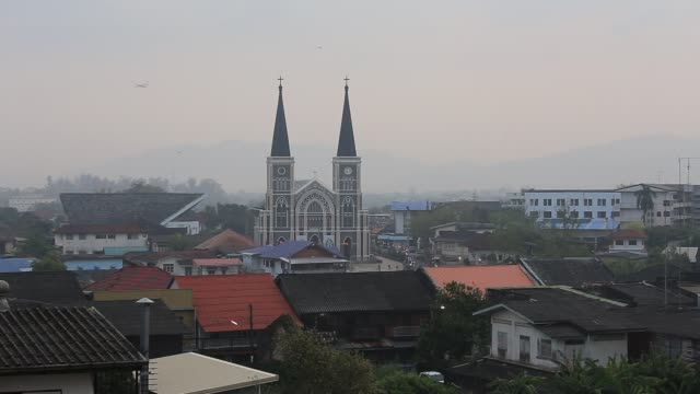 The Catholic Church and flying bird during morning mist at Chanthaburi Province, Thailand