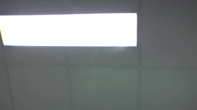 the ceiling and lights of a hospital corridor flow past from the point of view of a patient being moved on a bed. - ceiling stock videos & royalty-free footage