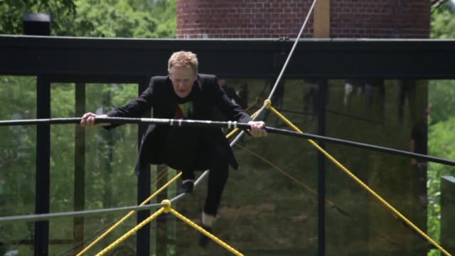 the celebrated tightrope walker philippe petit who in 1974 walked on a cable suspended between the twin towers in new york performs at the glass... - tightrope stock videos & royalty-free footage