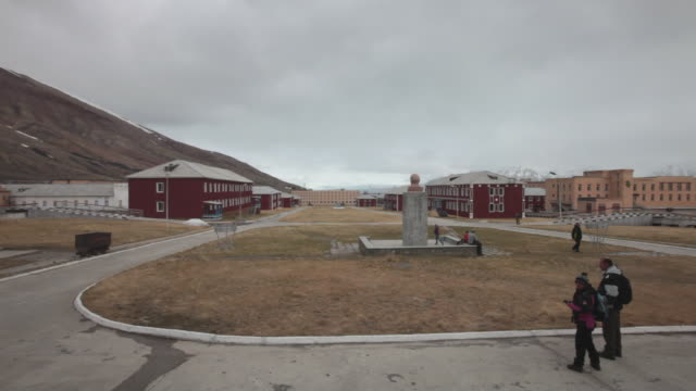The central square with the statue of Lenin looking at the Nordenskiöld glacier in the background in Pyramiden, a Soviet Ghost Town on the archipelago of Svalbard