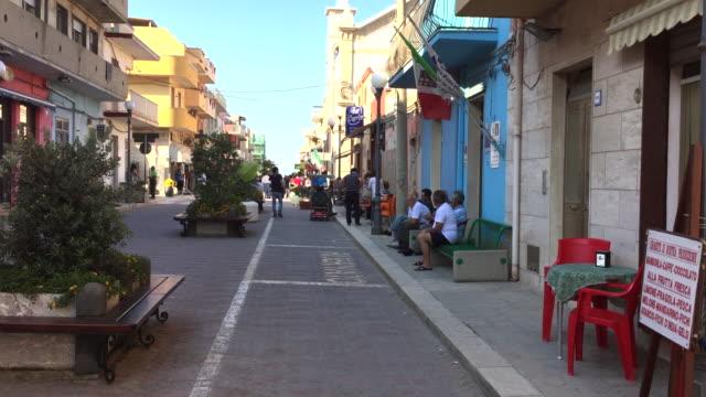 the central street of portopalo di capo passero in the evening, sicily - town video stock e b–roll