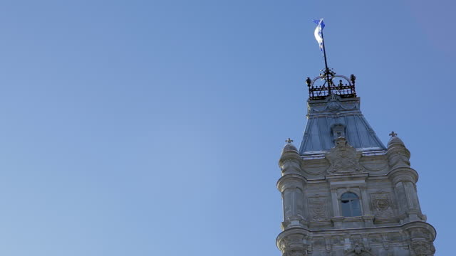 The central tower of the National Assembly with the Quebec flag half-masted waving