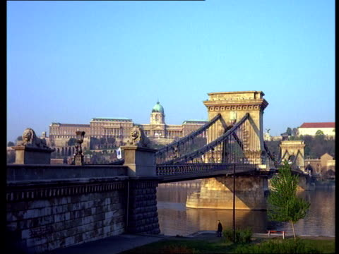 the chain bridge crosses the danube river near the royal palace in budapest, hungary - chain bridge suspension bridge stock-videos und b-roll-filmmaterial