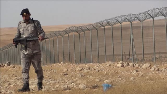 the chain link fences topped with coils of barbed wire rise and fall like a serpents back across the desert scrubland between saudi arabia and the... - kettenglied stock-videos und b-roll-filmmaterial