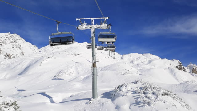 the chairlift at a snow covered mountain resort. - seggiovia video stock e b–roll