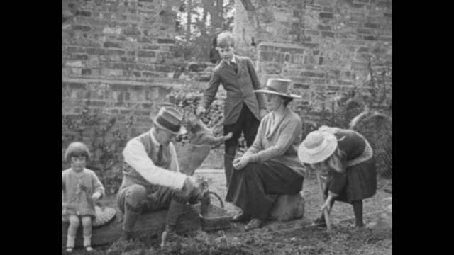 the chamberlain family together in a garden with dog running around behind and playing with the son they have tea at an outdoor table and sir austen... - veranda stock videos & royalty-free footage