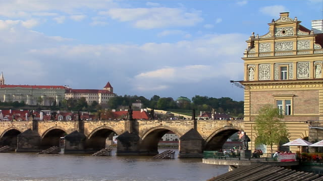 the charles bridge spans the vltava river in prague. - hradcany castle stock videos and b-roll footage