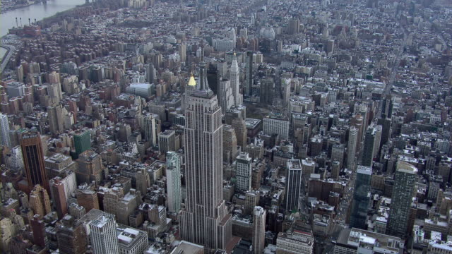 vidéos et rushes de the charming art deco forms of the empire state building rise above the other skyscrapers of midtown manhattan. - 1930