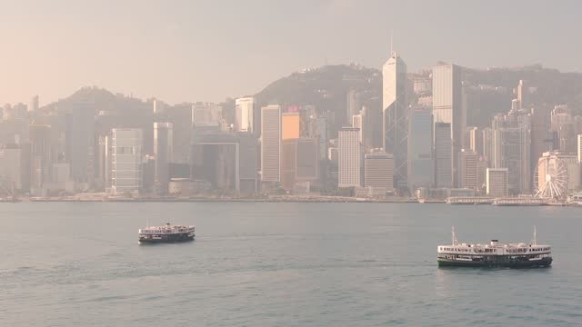 stockvideo's en b-roll-footage met the charming star ferry boats cruising across calm water in victoria harbour in hong kong with high rise buildings in the background on a foggy day - wide shot - hong kong