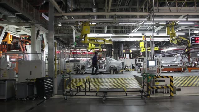 the chassis of a volkswagen ag vento automobile is lowered onto a production line an employee positions the side frames of volkswagen ag vento... - vento stock videos & royalty-free footage