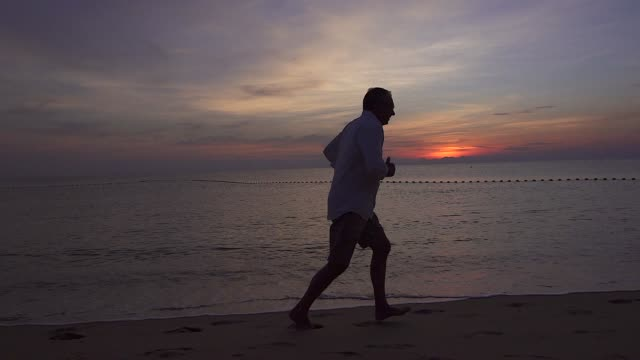 The cheerful fit senior man running at the beach in the morning