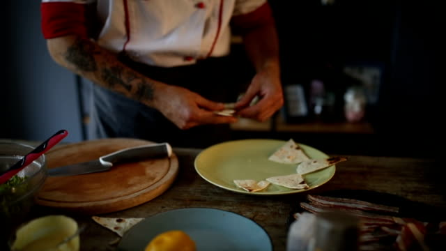 The chef is decorating plate with grilled tortilla