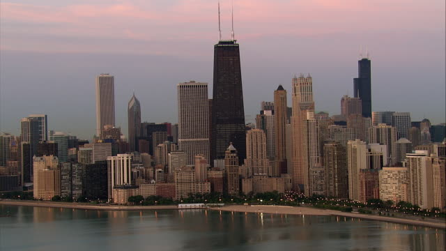 the chicago skyline rises against pink-hued clouds. - willis tower stock videos & royalty-free footage