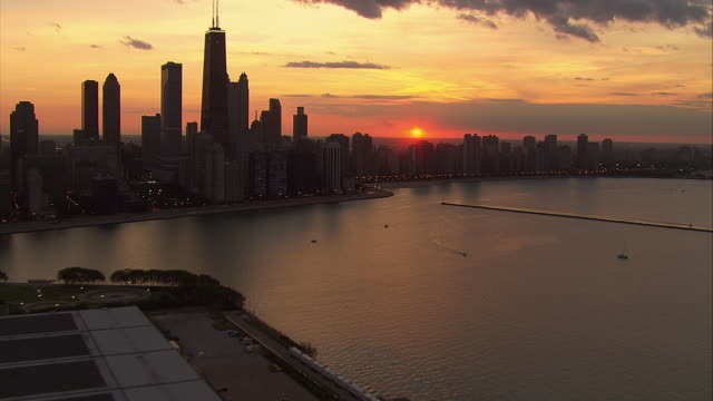 The Chicago skyline rises in silhouette above Lake Michigan.