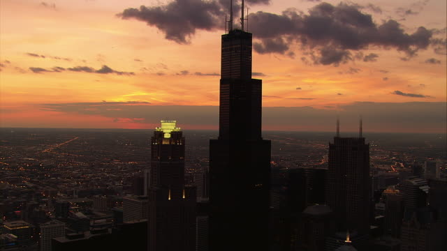 the chicago skyline rises in silhouette above lake michigan. - sears tower stock-videos und b-roll-filmmaterial