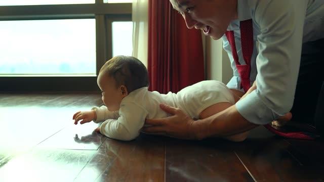 das kind versucht zu krabbeln. niedliches und liebenswertes neugeborenes baby versuchen, zu kriechen und vater folgen, um pflege zu nehmen. - subjektive kamera ungewöhnliche ansicht stock-videos und b-roll-filmmaterial