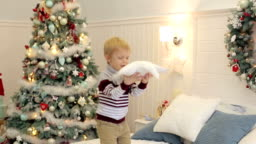 The child jumps on the bed near the Christmas tree